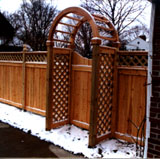 wood arbor with a gate and privacy fence by elyria fence