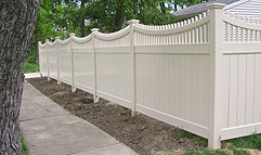 Vinyl privacy fence with scalloped spindle lattice by Elyria Fence