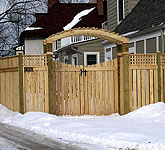 wood arbor with a gate and semi private wood fence by elyria fence